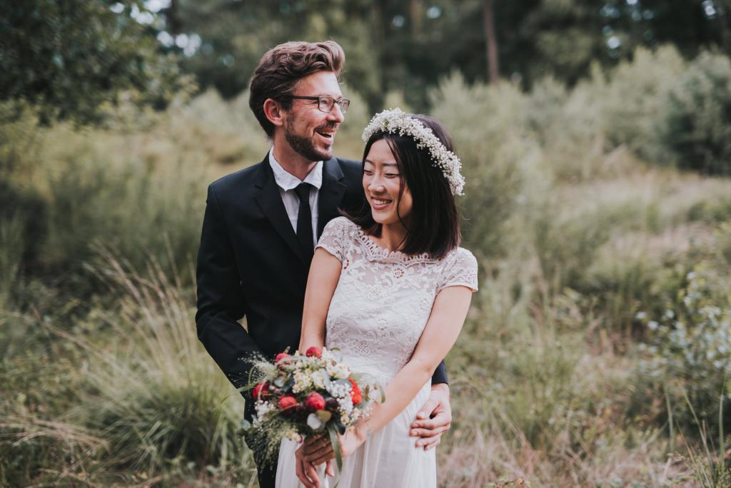 Kuschelndes Brautpaar mit Brautstrauß